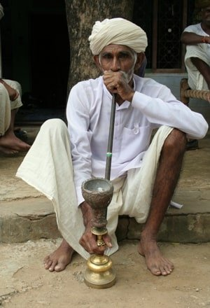 an old man in sitting position smoking from hookah