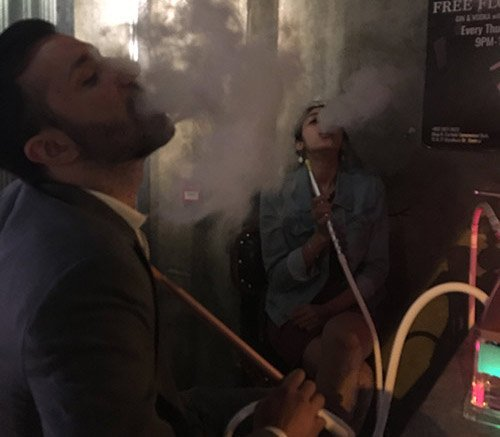 man and woman smoking shisha in a hookah lounge