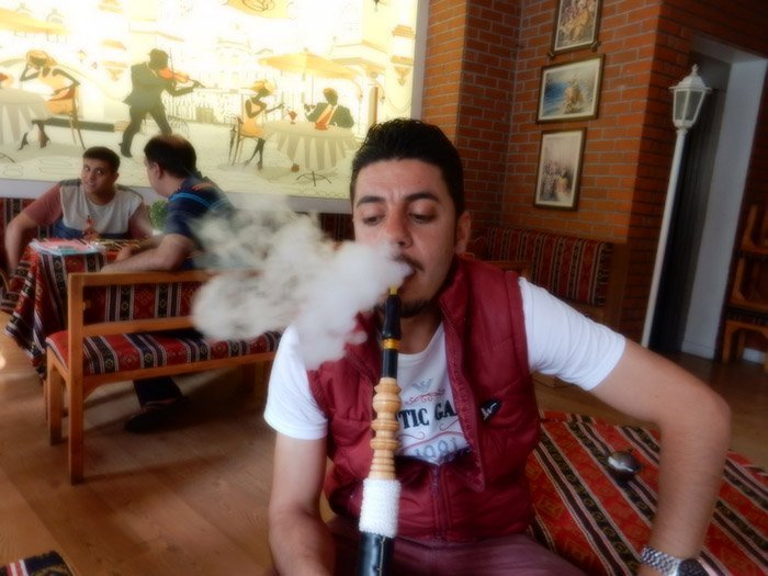 man smoking shisha in a hookah lounge