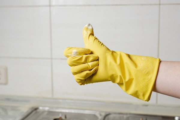 woman with yellow glove showing thumb up
