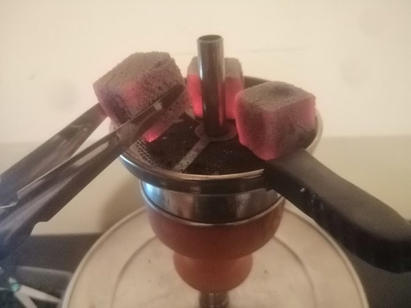 removing hookah coal from the top of the head
